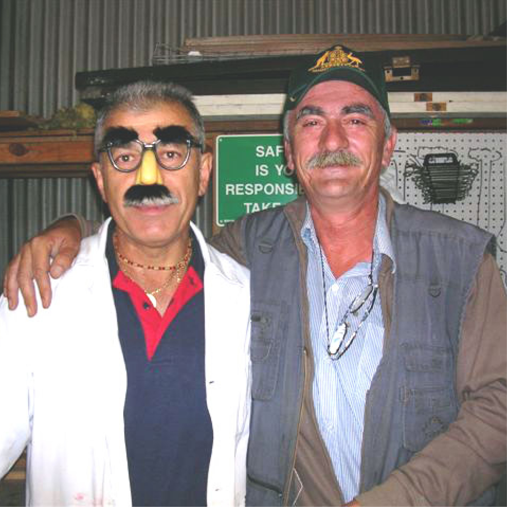 Close up of two older men, posing together. Both with a smiles and one wearing novelty glasses with big eye brows and nose.