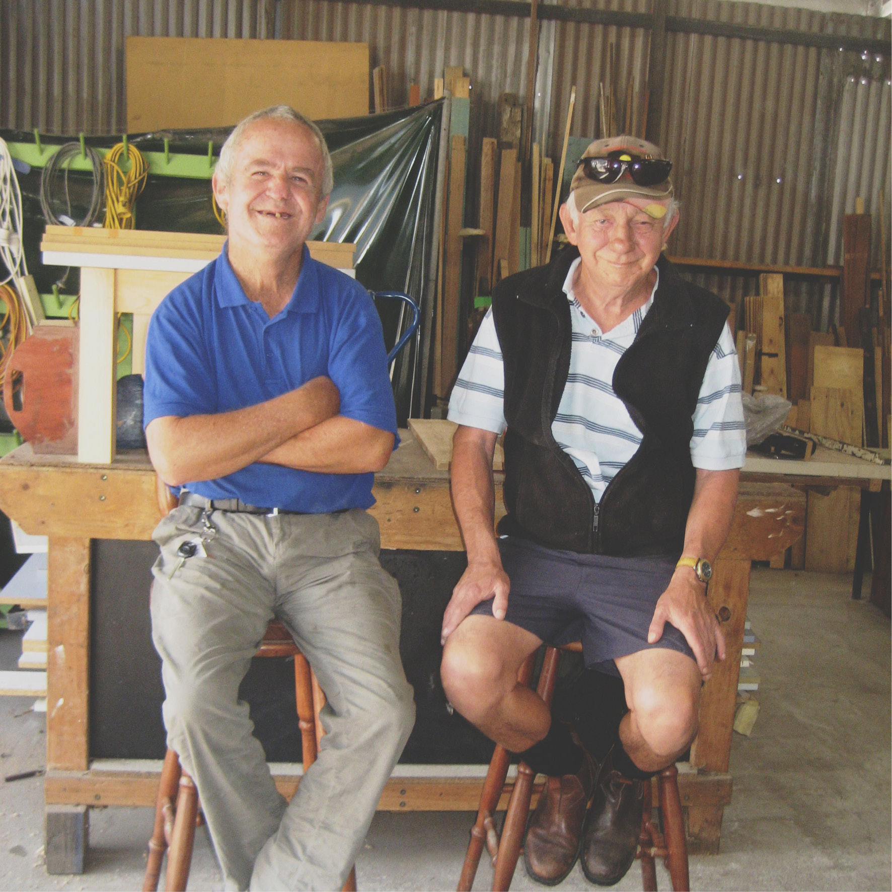 Two older men setting on stools inside a workshop/garage.