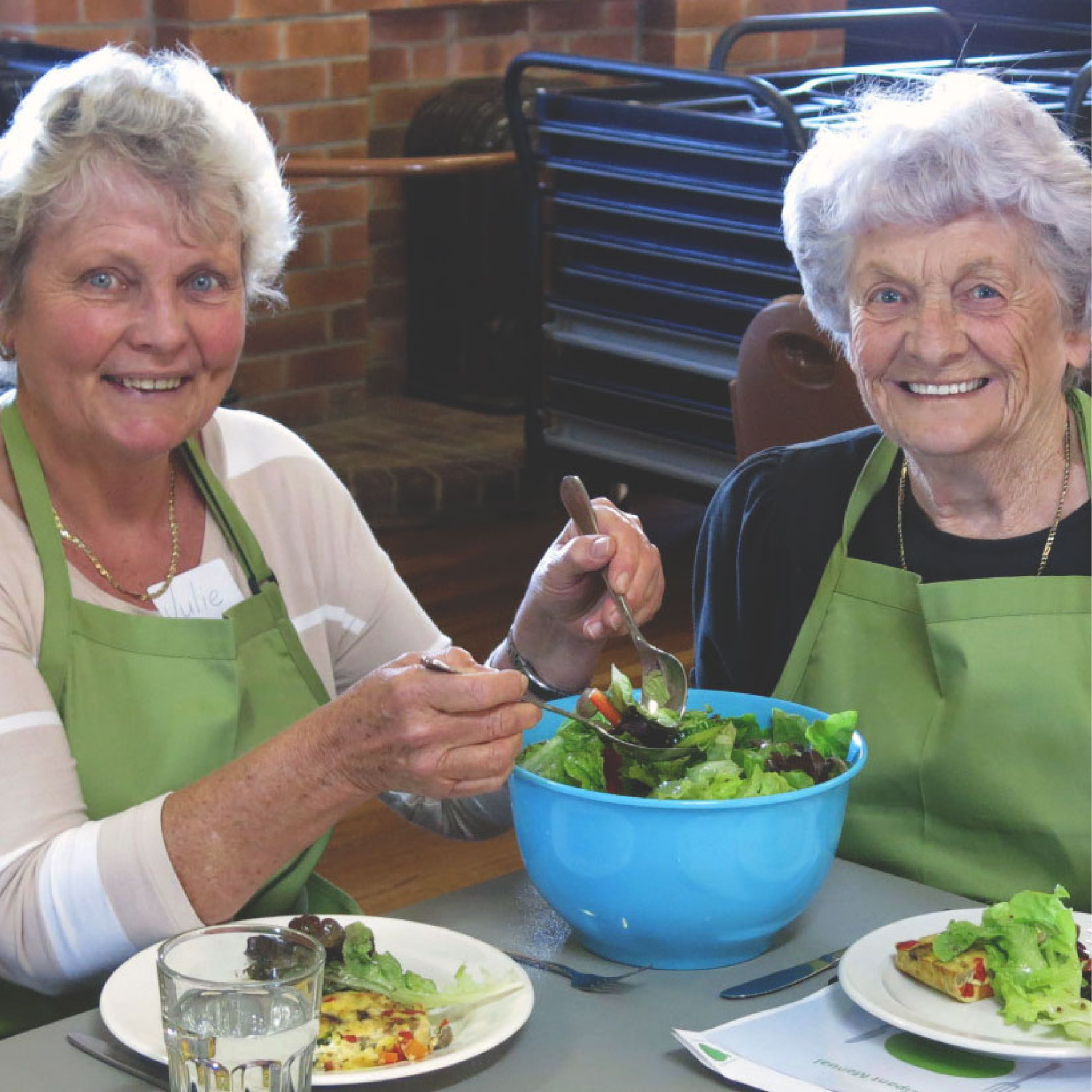 Two ladies mixing up a bowl of salad